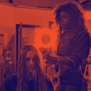 A photograph of a hairstylist preparing a models hair for a photoshoot