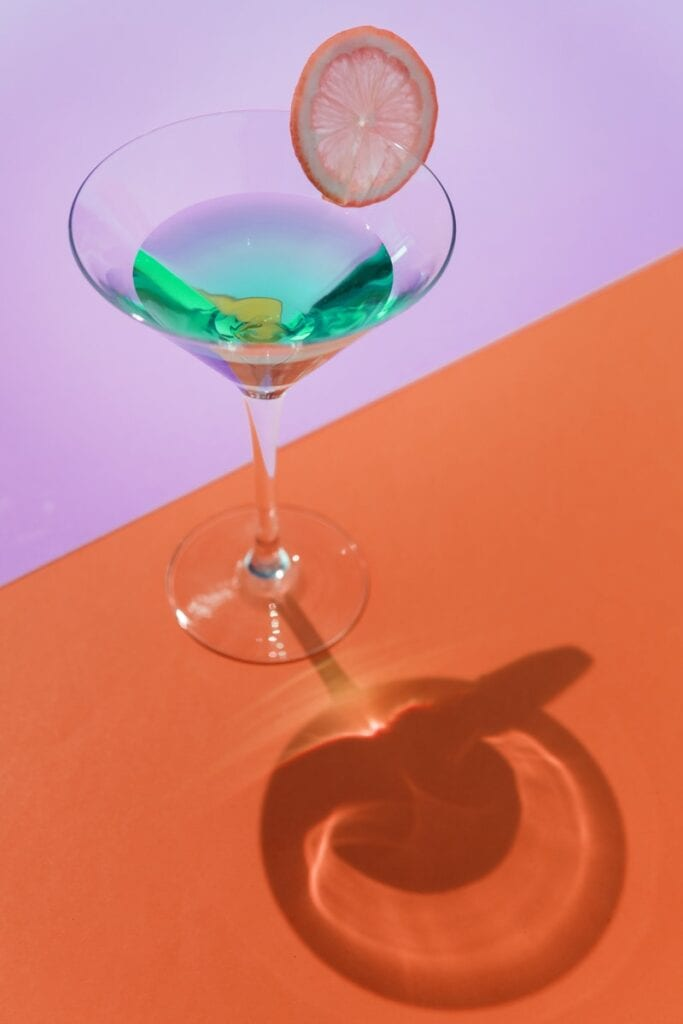 Photograph of a cocktail in a martini glass on a lilac and orange background