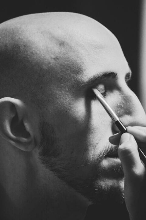 A bald man having concealer applied to his eyelid