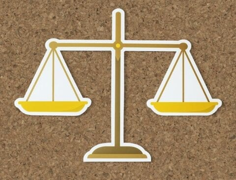 a cut our of scales on a cork background depicting ethics