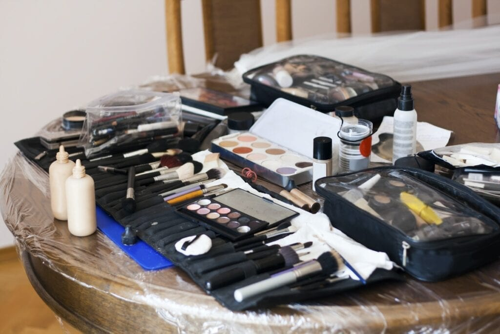 Photograph of a table with a makeup artists kit strewn across to illustrate the costs of free work as a beauty professional